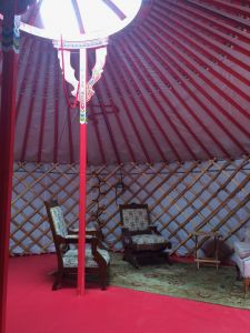 cosy set up of antique chairs in a red yurt